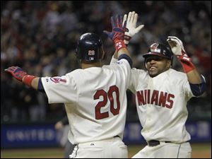 Cleveland's Carlos Santana, right, runs to congratulate Orlando Cabrera (20) after Cabrera's bases loaded single in the 13th inning gave the Indians a 3-2 win over the Detroit Tigers on Saturday.