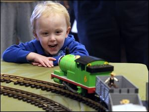 A model train set up for National Train Day meets the approval of Ethan Eidy, 3, of Sylvania. The daylong event included a talk by a railroad engineer that emphasized safety. Sponsors estimated attendance would total 5,000 for the day.