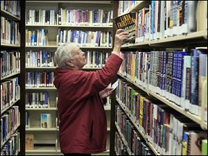 Jean Bertsch looks for books at the Birchard Public Library in Fremont. The library, which has branches in Woodville, Gibsonburg, and Green Springs, is seeking its first operating levy on Tuesday.