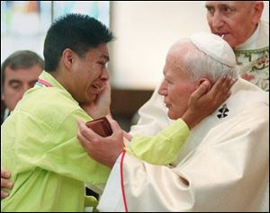 Pope John Paul II, right, greets a young man during a mass at the Cathedral of the Immaculate Conception in Denver in this Aug. 15, 1993 file photo.