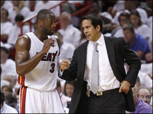 Miami Heat coach Erik Spoelstra, right, talks with Dwyane Wade during the first half of Game 1 of a second-round NBA playoff basketball series against the Boston Celtics Sunday in Miami.