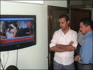 People watch a TV broadcast on the death of Osama bin Laden in Baghdad, Iraq.