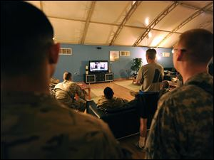 Army service members watch on television President Barack Obama talk about the death of Osama bin Laden inside the USO at Kandahar Airfield, Afghanistan.