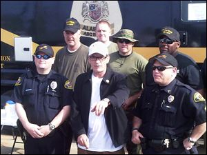 Actor Charlie Sheen poses with police officers and National Guard soldiers Monday in Tuscaloosa, Ala. Sheen said Monday he is organizing a relief event for tornado victims in this Alabama town.