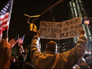 Herman Maisonave, of the Queens borough of New York, right, holds up a sign as he joins those gathered at ground zero in New York as they react to the news of Osama Bin Laden's death early Monday morning.