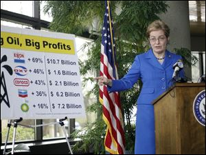 U.S. Rep. Marcy Kaptur gestures toward a chart showing major oil companies' profit increases. Speaking Sunday outside the Toledo-Lucas County Port Authority's offices, she called on the Speaker of the U.S. House to allow a vote on ending tax breaks for the companies.