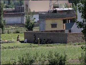 Pakistan army soldiers rest near the house where it is  believed al-Qaida leader Osama bin Laden lived in Abbottabad, Pakistan on Monday.