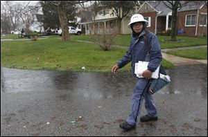 Rolando Buno skirts a pool of water in a front yard as he delivers mail in the rain along Heatherdowns Boulevard in mid-April. He said he's been braving the elements for 17 years.