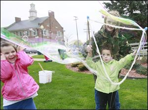 Taegen Payne, 5, of Newport, Mich., left, reacts to the expanding soap bubble made by Allison Callahan, 3, of Brighton, with the help of Kayleigh Adams, 13, of Monroe.