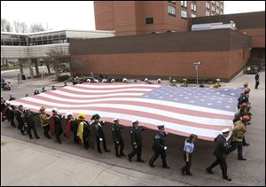 The Patriot Flag, a 30-by-60-foot flag honoring those who died in the terrorist attacks of Sept. 11, 2001, is carried up Ottawa Street in Lansing, Mich., to the Capitol where it will be displayed over downtown Tuesday.
