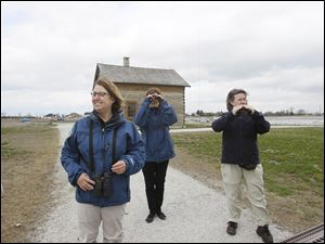 At Pearson Metropark, Karen Mitchell, left, Stacey Schamberger, center, and Heather Norris, each a Metroparks naturalist, stroll away from a cabin for a view of the aerial wildlife.