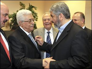 Palestinian President Mahmoud Abbas, center-left, and Hamas leader Khaled Mashaal, center-right, shake hands at a ceremony in Cairo, Egypt.