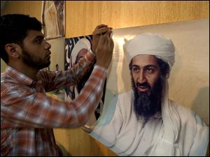 A Pakistani man hangs photos of al-Qaeda leader Osama bin Laden, taken by Pakistani photographer Mazhar Ali Khan, for display at the National Press Club in Islamabad, Pakistan.