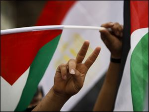 Palestinians gesture and wave the Palestinian and Egyptian flags Wednesday as they take part in a rally in the West Bank city of Ramallah celebrating the signing of a reconciliation agreement between Fatah and Hamas.