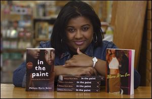Toledo native Philana Boles shows off two of her four novels, 'Blame It On Eve' and 'In The Paint.'