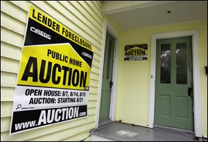 A home in Chagrin Falls, Ohio, has a foreclosure auction sign displayed in it.