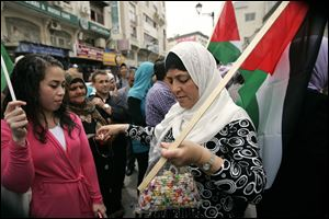 A Palestinian woman hands out candy Wednesday during a rally in Ramallah.