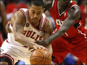 Newly-crowned MVP Derrick Rose of the Chicago Bulls, left, is hounded by Atlanta's Jamal Crawford in the fourth quarter Wednesday in Game 2. The Bulls pulled away late for a 86-73 win to even the series at one game apiece.