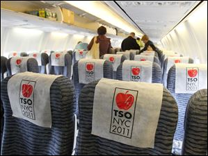 Sheets bearing the logo for the Toledo Symphony Orchestra's trip to Carnegie Hall cover the head rests on the plane.