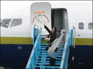 Amy Chang, a cellist with the Toledo Symphony Orchestra, waves as she boards a plane bound for New York City.