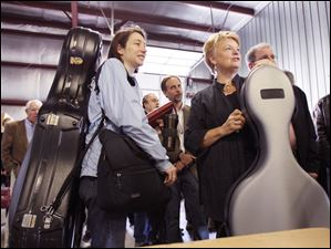 Renee Goubeaux, left, and Sally Dunning, cello players with the Toledo Symphony Orchestra, wait to board a plane at Toledo Express Airport.