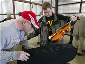 A TSA security officer, left, checks Tim Zeithamel's viola and instrument case prior to boarding the plane.