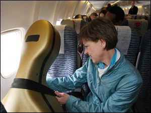 Martha Reikon, principal cellist with the Toledo Symphony Orchestra, fastens aseat belt around her cello before departure to New York.