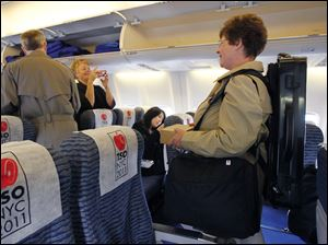 Nora Schankin, a bassoon player with the Toledo Symphony Orchestra, right, boards the plane.