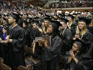 Graduates and guests applaud Air Force Staff Sgt. Joshua Falso after his commencement speech at Bowling Green State University in Bowling Green, Ohio. Sergeant Falso attended BGSU online while serving in various states and countries, including Iraq and Kuwait.