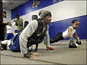 Allah Wright, left, and Wayne Lawrence Jr., known to many as Pretty Boy Bam Bam, do some push-ups while training at the Bang Em or Hang Em boxing gym.