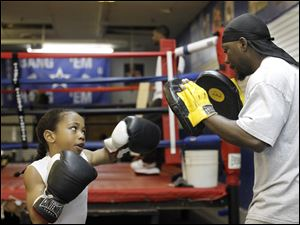 Wayne Lawrence Jr., left, known to many as Pretty Boy Bam Bam, and his father Wayne Lawrence Sr., right, spar while training.