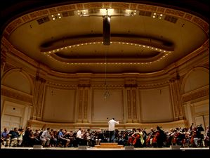 Under the direction of Principal Conductor Stefan Sanderling, members of the Toledo Symphony rehearse at Carnegie Hall.