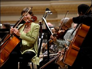 Cello player Martha Reikow shares a light moment with fellow musician Damon Coleman, right, as members of the Toledo Symphony prepare during a rehearsal Saturday for an evening performance at Carnegie Hall in New York. The performance will also include the Cold War-themed political play, Every Good Boy Deserves Favour as part of the program, with actors taking the stage with the orchestra.