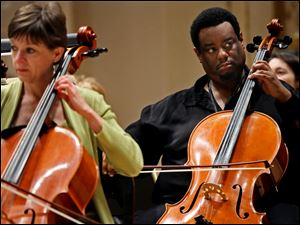 Cello players Martha Reikow, left, and Damon Coleman prepare during rehearsal with the Toledo Symphony.