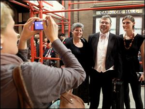 Violinist Tom Sieberg poses with his wife, Colleen, and daughter Megan, right, as Annika Michaels takes their picture.