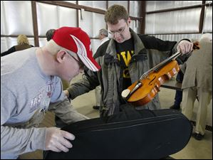 Tim Zeithamel, a viola player with the Toledo Symphony Orchestra, has his instrument case checked by a TSA security officer before boarding a plane at Toledo Express Airport on Friday