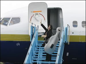 Cellist Amy Chang waves good-bye to Toledo before she boards the plane at Toledo Express Airport.