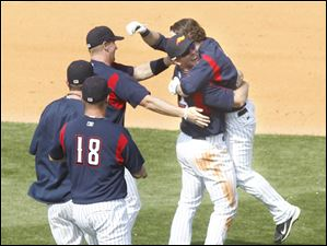 Toledo Mud Hens' Ryan Strieby picks-up Will Rhymes after Rhymes drove in the winning run.