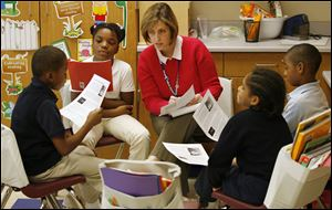 Diane Pickering, an intervention assessment teacher, oversees a group of students at Spring Elementary School. Third grader Antonia Lopez, 10, next to Ms. Pickering, was 'leading' the group, which included Daniel Combs, 10, left, Russell Bland, 8, and Terrell Newble, 8. The lesson is part of the Reading Academy Intensive Support Education program that aims to boost reading scores.