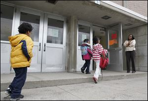 Students arrive for a school day at Pickett Academy under the watchful eye of Principal Martha Jude. In 2008, after years of failing test scores, officials in the Toledo Public Schools system remade Pickett, replacing most of its teachers and leadership, hoping to turn the school around.