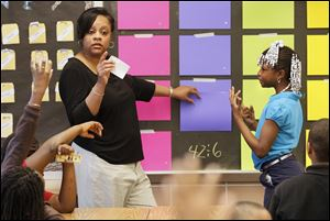 Teacher Donna Garth waits for an answer from Jazzlyn Whitlow, 9, right, during a 'Jeopardy'-like math game in her third-grade classroom at Pickett Academy. Pickett is Toledo's most chronically poor performing school, but a closer look at the data shows students at the central-city school are making progress.