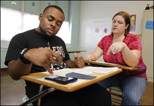 Scott High School's Denzel Moore, left, uses his calculator to figure a math conversion problem as teacher Melody Basta looks on.
