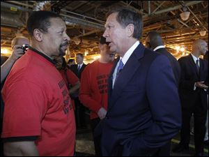 Ray Wood, president of UAW Local 14, left, and Gov. John R. Kasich, right, speak after the announcement.