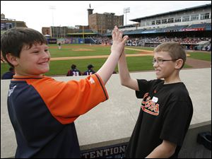 Dylan Altman, left, 11, and Mitch Gable, 11, both fifth graders at Miller City School, high-five as the Toledo Mud Hens take the field against the Lehigh Valley IronPigs.