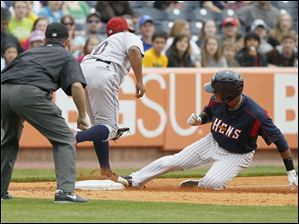 Toledo Mud Hens player Argenis Diaz, 11, is slides safely into third base with a triple as Lehigh Valley IronPigs player Ronnie Belliard, 10, wrangles the throw during the ninth inning.