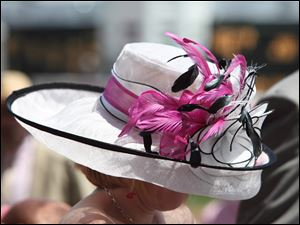 A flash of hot pink accentuates the traditional black and white of a Derby spectator's hat.