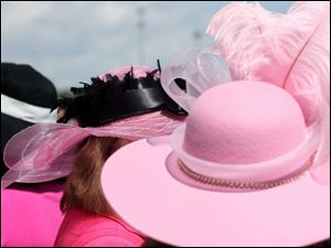 Women's hats are bedecked with feathers, ribbons, and jewels at Churchill Downs for the 2011 running of the Kentucky Derby.