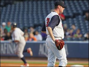 Mud Hens pitcher Charlie Furbush looks away as IronPigs player Tagg Bozied rounds the bases after hitting a home run during the first inning.
