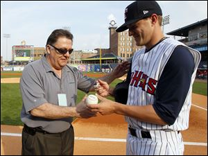 Mud Hens pitcher Adam Wilk signs a baseball for  Toledo Blade sports editor Frank Corsoe after throwing out the first pitch before the Hens play the Lehigh Valley IronPigs at Fifth Third Field.