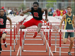 DerJuan Gambrell of Rogers, center,  wins the 110 meter hurdles against Roger's Jerrette Bradley, left, and Oregon Clay's Noah Buehrer during the City League track meet at Rogers.